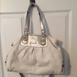 A white coach handbag with silver trim